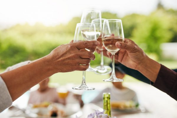 Closeup of of a group of unrecognizable people having a celebratory toast with wine around a table at home during the day